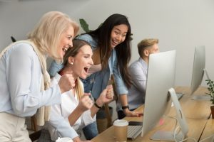 Diverse team excited by online win or business achievement