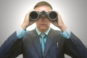 Businessman in suit with binoculars in hand