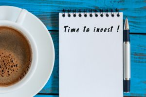 """Cup of coffee, pen and notepad saying """"Time to invest"""" on a table"""